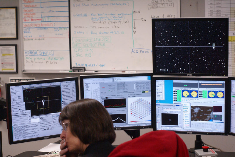 A telescope operator in the HET control room. The large monitor at top right shows the telescope's field of view. Other monitors show weather, the state of the telescopes 91 mirrors, and other data.